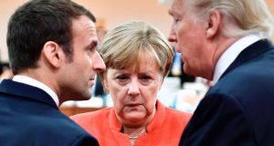French president Emmanuel Macron, German chancellor angela merkel and us president Donald Trump confer at the start of the first working session of the G-20 summit in Hamburg, Germany, yesterday. Photograph: John Macdougall/Pool/The New York Times