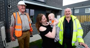 Helen Cheevers with baby Erik outside her new home at Baile na Laochra in Ballymun, Dublin, with Hugh Brennan (l) of the Ó Cualann Cohousing Alliance and architect Joe Kennedy. Photograph: Cyril Byrne