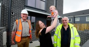 Helen Cheevers with her baby Erik outside her new home at Baile na Laochra, Ballymun, with Hugh Brennan of Ó Cualann co-housing alliance, and architect Joe Kennedy of Smith Kennedy Architects. Photograph: Cyril Byrne