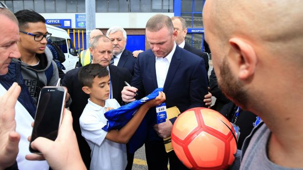 Wayne Rooney signs autographs outside Goodison Park. Photograph: Nigel french/PA