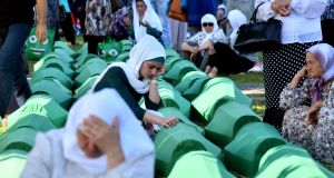 Bosnian Muslim women offers prayers near the coffins of 71 victims of the 1995 Srebrenica massacre, at the memorial cemetery in the village of Potocari, near Srebrenica, on Tuesday. Photograph: Elvis Barukcic/AFP/Getty Images