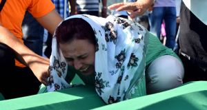 A Bosnian Muslim women expresses her grief as she mpourns over the casket of her brother, one of 71 victims of the 1995 Srebrenica massacre, at the memorial cemetery in  Potocari on Tuesday. Photograph: Elvis Barukcic/AFP/Getty Images