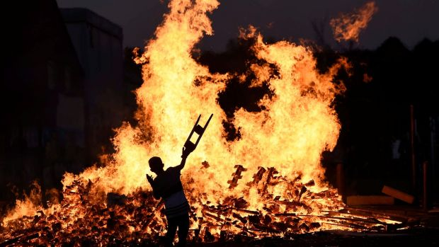 A child throws bits of wood onto a bonfire during the Twelfth of July celebrations. Photograph: Reuters