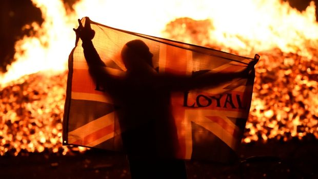 A man holds a Union flag in front of a bonfire in the Sandy Row area. Photograph: Reuters