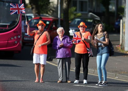 Members of the public watch as Orange Order members march past Ardoyne shops on the Crumlin Road in Belfast. Photograph: Niall Carson/PA Wire