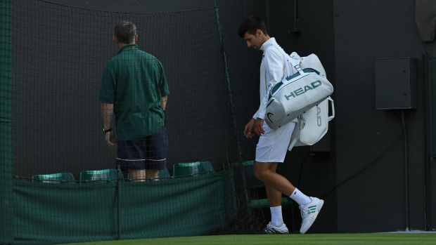 Djokovic leaves the court after retiring in his loss to Berdych. Photo: Glyn Kirk/Getty Images