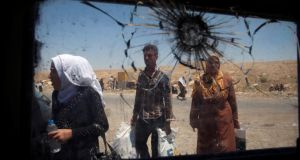 Displaced Iraqi civilians seen through a shattered window of an Iraqi forces vehicle in Mosul. Photograph: Erik De Castro/Reuters