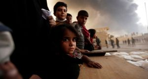 Displaced children wait to receive food supplies at a processing centre in Qayyara, south of Mosul. Photograph: Zohra Bensemra/Reuters