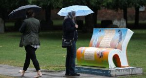 People shelter under umbrellas as they look at a Jane Austen-inspired bench outside Winchester Cathedral in Hampshiresssss which is part of the 'Sitting with Jane' art trail to commemorate the 200th anniversary of her death.  Photograph:  Andrew Matthews/PA Wire