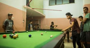 Palestinian youths play pool on Tuesday this week during the few hours of mains electricity the residents of the Gaza Strip enjoy  every day. Photograph: Mahmud Hams/AFP/Getty Images
