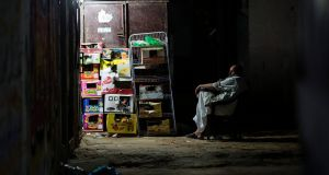 A Palestinian  sits outside his shop on Tuesday this week during the few hours of mains electricity the residents of the Gaza Strip enjoy every day. Photograph: Mahmud Hams/AFP/Getty Images