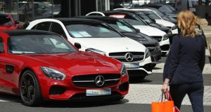 A woman walks past Mercedes cars at a dealership in Berlin on July 13th. German media say  Daimler AG possibly installed emissions cheating software into a million Mercedes vehicles. Photograph: Getty