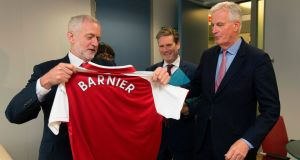 British Labour Party leader Jeremy Corbyn presents an Arsenal football jersey to EU Brexit negotiator Michel Barnier. Photograph:   Olivier Hoslet/Getty Images