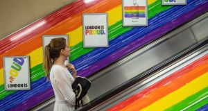 A  woman rides a tube escalator decorated with the Pride flag colours. Photograph: Getty Images