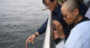 A handout photo provided by the Shenyang Municipal Information Office shows late Nobel laureate Liu Xiaobo's wife Liu Xia (right) praying as they bury Liu's ashes at sea. Photograph: AFP