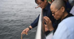 Nobel laureate Liu Xiaobo's wife Liu Xia prays as Chinese officials bury her husband's ashes at sea off the coast of   Dalian, Liaoning Province, on Saturday. Photograph: AFP/Getty Images