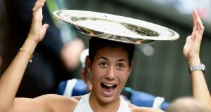 Garbine Muguruza of Spain celebrates with her trophy after defeating  Venus Williams  7-5 6-0 to win the women's singles title at Wimbledon. Photograph: Gerry Penny/EPA