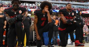 Colin Kaepernick (centre): refused to stand for the national anthem in support of the Black Lives Matter protest – a move that has effectively stalled his career.