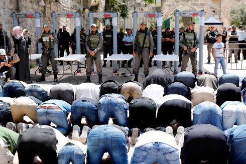 REOPENED: Palestinians pray in front of the new security metal detectors as Israeli border police personnel stand guard at the entrance to the al-Aqsa compound in Jerusalem's Old City. Israel reopened the holy site after it was closed for Friday prayers after the fatal Palestinians shooting attack.  PhotographL Abir Sultan/EPA