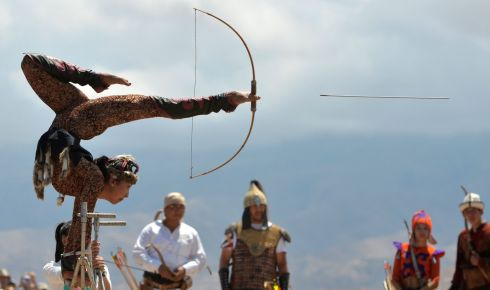 BEST FOOT FORWARD: A Kyrgyz woman balances on her hands as she shoots a bow and arrow with her feet during the 'Ethno Fest' festival in the village of Ton. Photograph: Vyacheslav Oseledkovyacheslav/AFP/Getty Images