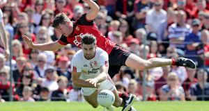 Down midfielder Peter Turley tumbles over  Tiernan McCann of Tyrone during the Senior Football Championship Final in St Tiernach's Park, Clones, Co Monaghan. Photograph: Morgan Treacy/Inpho