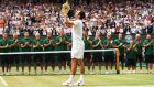 Roger Federer lifts his eighth Wimbledon title. Photograph: Clive Brunskill/Getty