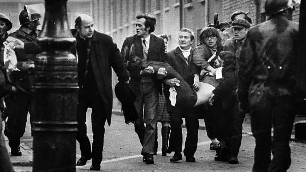 Bishop Daly helps clear a path for a man badly injured during Bloody Sunday in Derry.