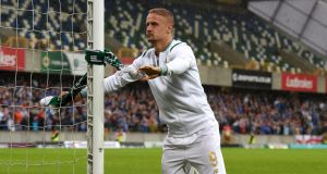 Leigh Griffiths ties a Celtic scarf around the goal post after the Champions League second round first leg qualifying game against Linfield at Windsor Park. Photgraph:Getty Images