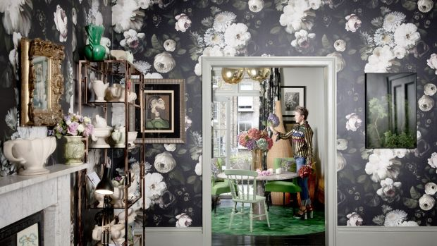 The walls are covered in a huge floral print wallpaper by Ellie Cashman