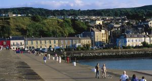 Tourists walking on seawall, Howth Harbour, Dublin
