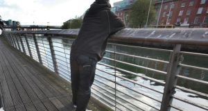 A man looks out over the Rivey Liffey from the adjacent boardwalk in Dublin. A victim of an alleged rape  and a suspect met by chance on the boardwalk last  Saturday afternoon. File photograph: Brenda Fitzsimons/The Irish Times