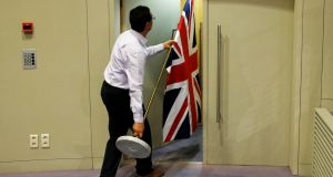 An official carries a Union Jack flag ahead of a news conference in Brussels by Britain's Brexit secretary  David Davis and EU Brexit negotiator Michel Barnier. Photograph:  Reuters/Francois Lenoir