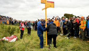 Rules officials help remove a signpost to allow Rory McIlroy  play a shot on the 15th hole during the second round of the 146th Open Championship at Royal Birkdale. Photograph: Dan Mullan/Getty
