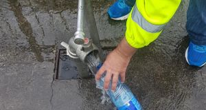 A Louth County Council worker helps fill bottles with water at one of the temporary water stations in Drogheda. Photograph: Paddy Logue