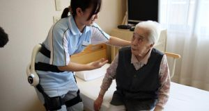 A care worker wearing   Cyberdyne's robot suit which learns a  user's motion and assists their movements. Photograph: Yoshikazu Tsuno/AFP