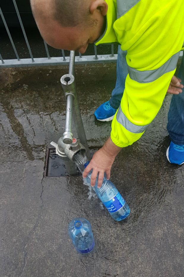 "A Louth County Council worker fillilng water at a ""temporary water station"" on Bóthar Brugha, Drogheda. Photograph: Patrick Logue"