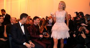 Lionel Messi and Cristiano Ronaldo look on as Stephanie Roche arrives for the 2014 Fifa Ballon d'Or Gala. Photograph:  Alexander Hassenstein/Getty Images