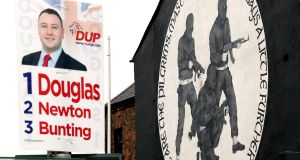 A loyalist paramilitary mural is seen with a DUP election poster in east Belfast, in March. Photograph: Paul Faith / AFP / Getty Images