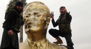 Fighters loyal to al-Qaeda's Syrian affiliate, Tahrir al-Sham (then known as Jabhat al-Nusra) and its allies smash a statue of the late Syrian president Hafez al-Assad in Idlib in March 2015. Photograph: Sami Ali/AFP/Getty