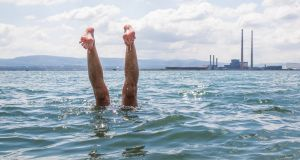 ANYTHNG YOU CAN DO... A swimmer's legs mirror Poolbeg's chimneys at the men's bathing shelter in Bull Island. Photograph: Fran Veale