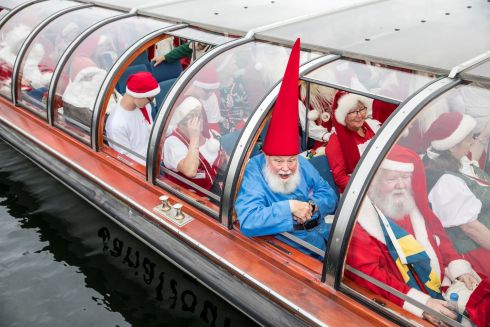 I'M SANTA CLAUS, NO I'M SANTA CLAUS: People dressed as Santa Claus take a canal tour of Copenhagen during the World Santa Claus Congress, an event held every summer at the amusement park Dyrehavsbakken, in Denmark. Photograph: Scanpix Denmark/Nikolai Linares/Reuters