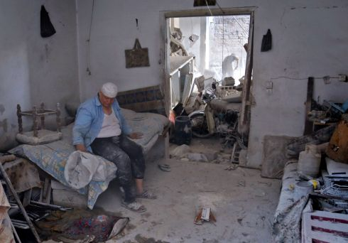 PICKING UP THE PIECES: A Syrian man sits in his house following an air strike late the previous night on the rebel-held town of Arbin, east of the capital. Photograph: Abdulmonam Eassa/AFP/Getty Images