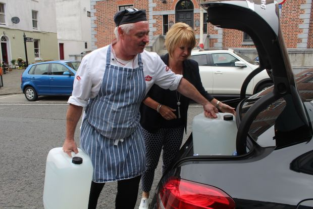 Chef Brian Malone and Relish cafe owner Denise Walsh unload tanks of water from a local car wash to use in her coffee shop in Drogheda. Photograph: Simon Carswell