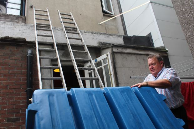 Martin McGowan, owner of Scholars Townhouse Hotel in Drogheda, with a new water tank he is installing in his hotel to cope with the water crisis.