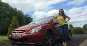 Niamh Towey with her car, which now has a back window and a fully complete exhaust system