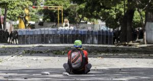 A demonstrator sits in front of a line of Bolivarian National Guard officers in Caracas, Venezuela. Photograph: Nathalie Sayago/EPA