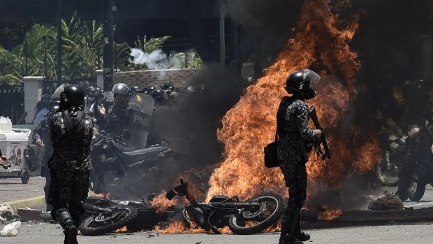 Bolivarian police officers stand in front of burning vehicles after an explosion in Caracas, Venezuela on Sunday. Photographer: Carlos Becerra/Bloomberg