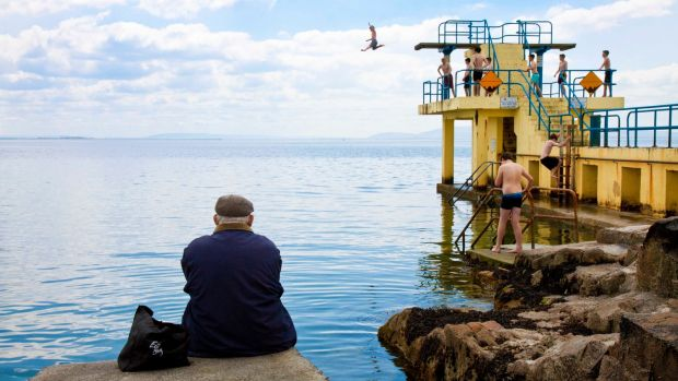 A man watches people jump off the diving platform at Blackrock, Salthill, Co. Galway. Photograph: Andy Newman