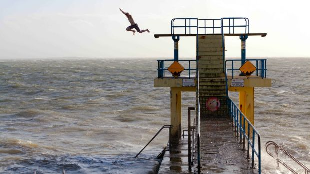 A teenager jumps off the diving platform at Salthill as storm 'Henry' approaches. Photograph: Andy Newman.