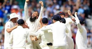 England's Moeen Ali is mobbed by his team-mates  after claiming  a sensational hat-trick against South Africa during the third Test at the Oval in London. Photograph:  Nigel French/PA